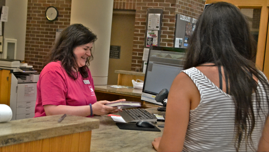 Staff member helping patron at front desk
